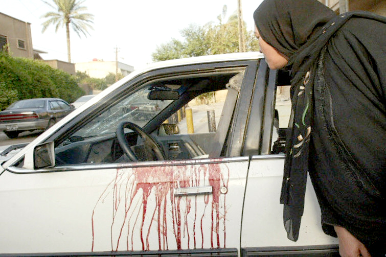 """An Iraqi woman peeps inside a blood stained car of two women allegedly shot dead by private security guards in central Baghdad, 09 October 2007. Foreign security guards killed two women when they opened fire on a car in the centre of the Iraqi capital today, witnesses and Iraqi security officials said. The shooting in Karrada came two days after Iraq vowed to punish US security firm Blackwater after a probe found that its guards were not provoked when they opened """"deliberate"""" fire in Baghdad three weeks ago, killing 17 Iraqis. It was not clear which security company was involved in today's shooting, which occurred at the Masbar intersection in Karrada, a commercial and residential district which is regarded as one of the most secure in Baghdad. AFP PHOTO/ALI YUSSEF (Photo credit should read ALI YUSSEF/AFP/Getty Images)"""